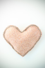 Pink handmade textile fabric heart on white background closeup