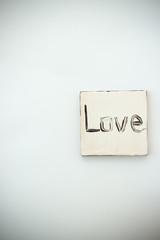 Black love text on handmade white jewellery closeup, background