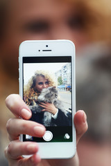 Young woman holding smartphone with the photo of herself and cat