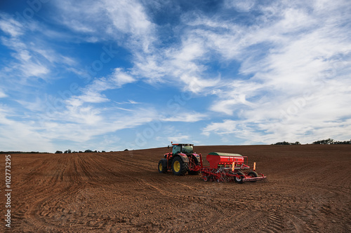 Wall mural Farmer with tractor seeding crops at field