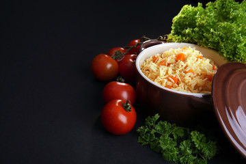 Stewed rice with a carrot and tomatoes in a cooking pot over black background