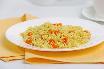 Stewed rice with a carrot on a white plate, close up