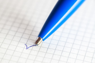 The end of a ballpoint pen on notebook background. Close-up