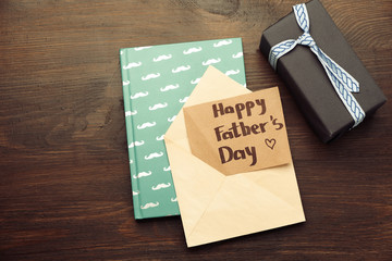 Happy Father's Day card, a gift box and notebook with mustache print on wooden background