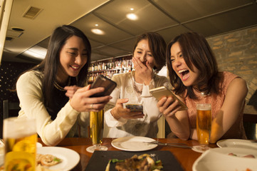 Three women are laughing while looking at the smartphone