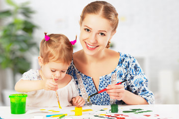 mother and child  daughter draw paints