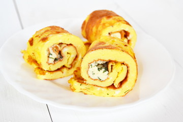 Rolls of omelette with cheese on a plate on white wooden background