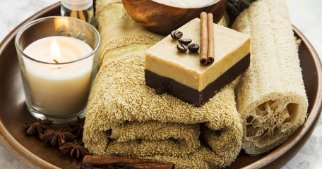 Spa-care products with coffee and cinnamon soap, towel and candl