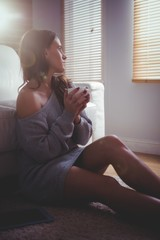 Beautiful brunette drinking coffee with tablet