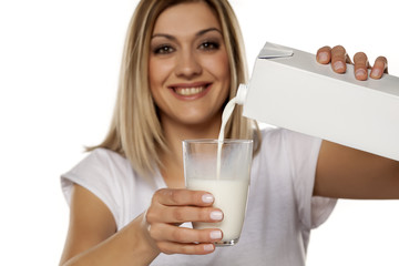 smiling young woman pours milk in a glass