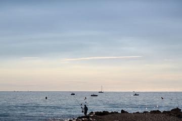 Fisherman on seascape background