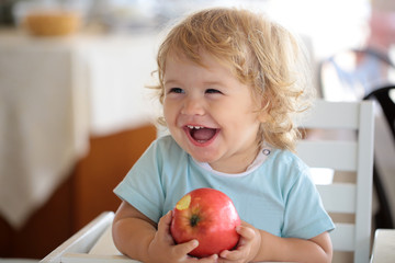 Laughing baby boy with apple