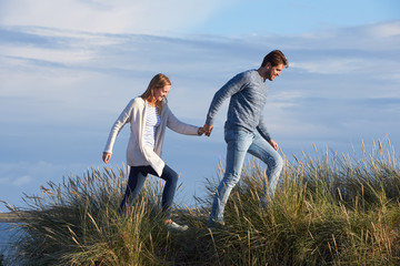 Couple Walking Through Sand Dunes Together