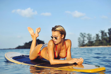 Sexy female model on surfboard in sea