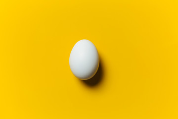 White egg on the yellow background in center