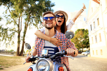 Portrait of happy young couple on scooter enjoying road trip Wall mural