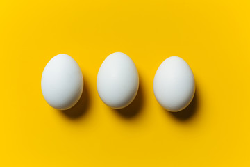 Three white egg on the yellow background
