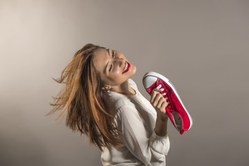 Cheerful attractive teen girl sing song holding a red shoe like a microphone holding it near her face, studio shot against gray background