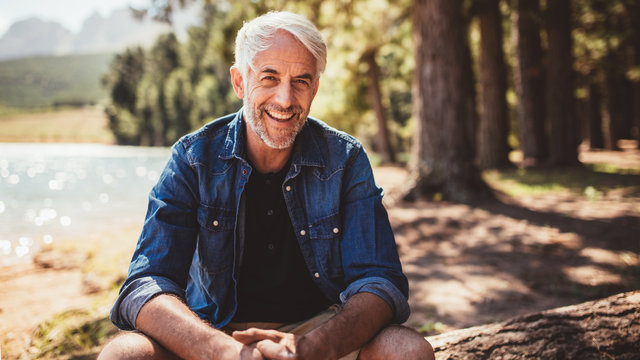 Happy mature man sitting near a lake