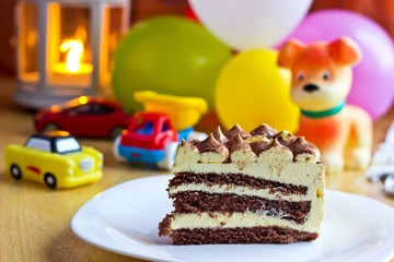 Baby boy first birthday party. Focus on cake with blurred multicolored background