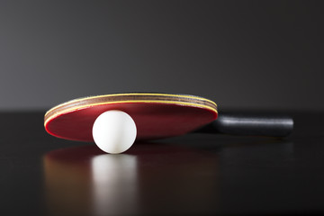 ping pong racket and ball on dark table