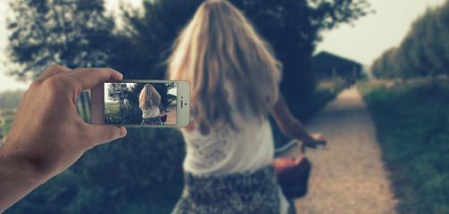 Männliche Hand haltet ein weißes Smartphone und fotografiert