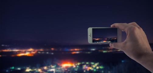 Männliche Hand haltet ein weißes Smartphone und fotografiert eine Stadt bei Nacht