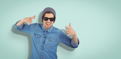 Composite image of happy hipster showing rock and roll hand sign