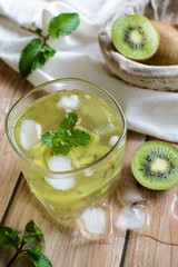 glass of refreshing tropical kiwi soda with mint