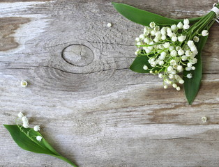 Decorative border or frame with lily of the valley flowers on a wooden background. Photo from above.