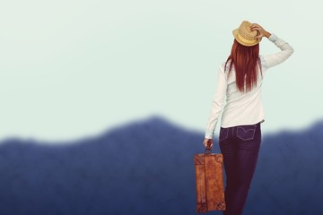 Composite image of rear view of hipster woman holding suitcase