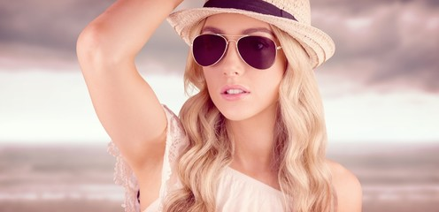 Composite image of gorgeous blonde hipster posing with straw hat