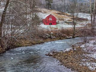 red barn in winter near a mountain river