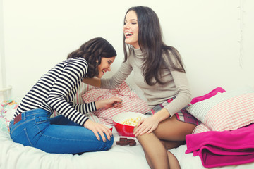 Two beautiful teenage girls laughing and gossiping on bed