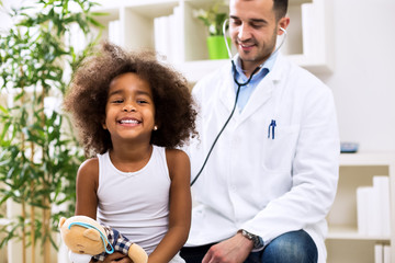 Doctor pediatrician examining cute smiling african girl