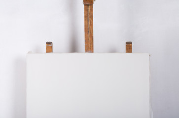 A white canvas in studio on an easel
