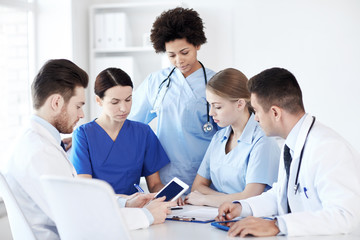 group of doctors with tablet pc at hospital