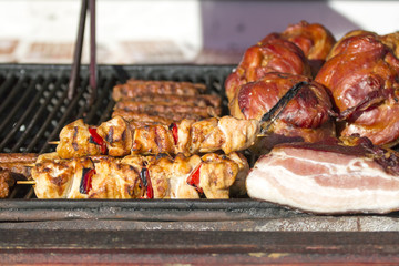 Different kind on grilled meat and sausages with smoke and steam from the grill