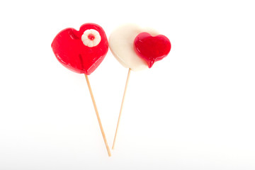 Colourful lollipop in the shape of a heart isolated on white background, a festive treat, a gift favorite, original declaration of love, the abuse of sweets faces caries