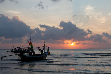Landscape photo of sun setting into the ocean with fishing boats are floating in the ocean