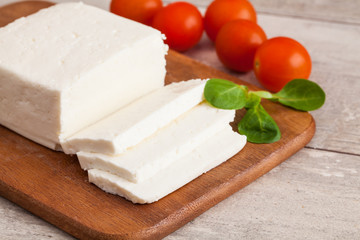 Traditional Greek Feta cheese and tomato on wooden table