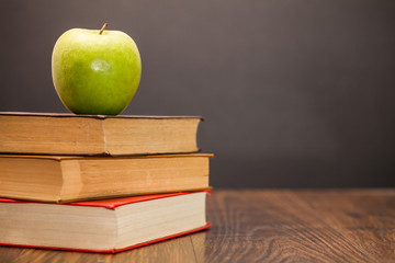 apple and book on wooden table