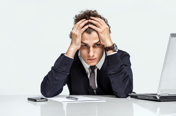 Entrepreneur dissatisfied with his earnings, profit, income, gain, benefit, margin / modern businessman at the workplace working with computer on grey background. Depression and crisis concept