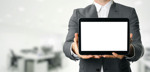 businessman holding blank digital tablet with copy space in offi