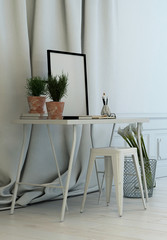 Simple writing table in front of long drapes