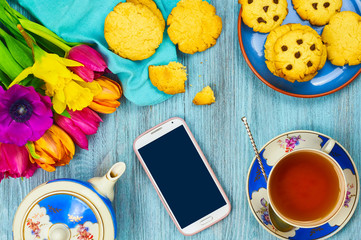 Smartphone and cup of tea with cookies. Composition decorated with flowers on wooden background. Top view. Close-up. Selective focus