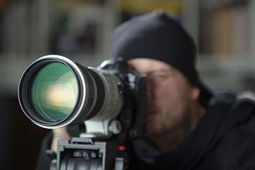 Man taking pictures with large telephoto lens