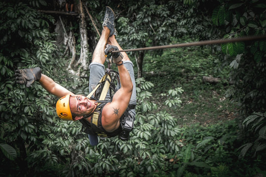 Strong smiling young man zipline in jungle