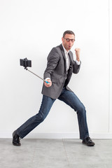 male corporate selfie - dynamic middle aged businessman fighting for fun in taking selfie with a stick at work over white background office...