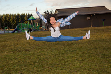 Active young girl jumping and doing the splits midair